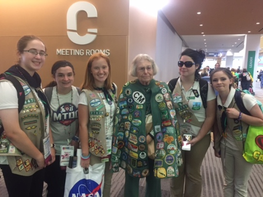 Five teen girls and woman wearing Girl Scout gear stand inside smiling.