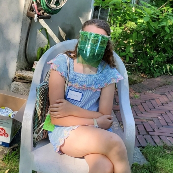 Teen girl sits outside wearing homemade face shield.