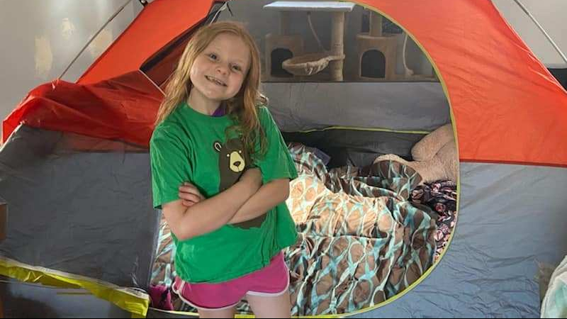 Young girl stands smiling indoors next to tent.